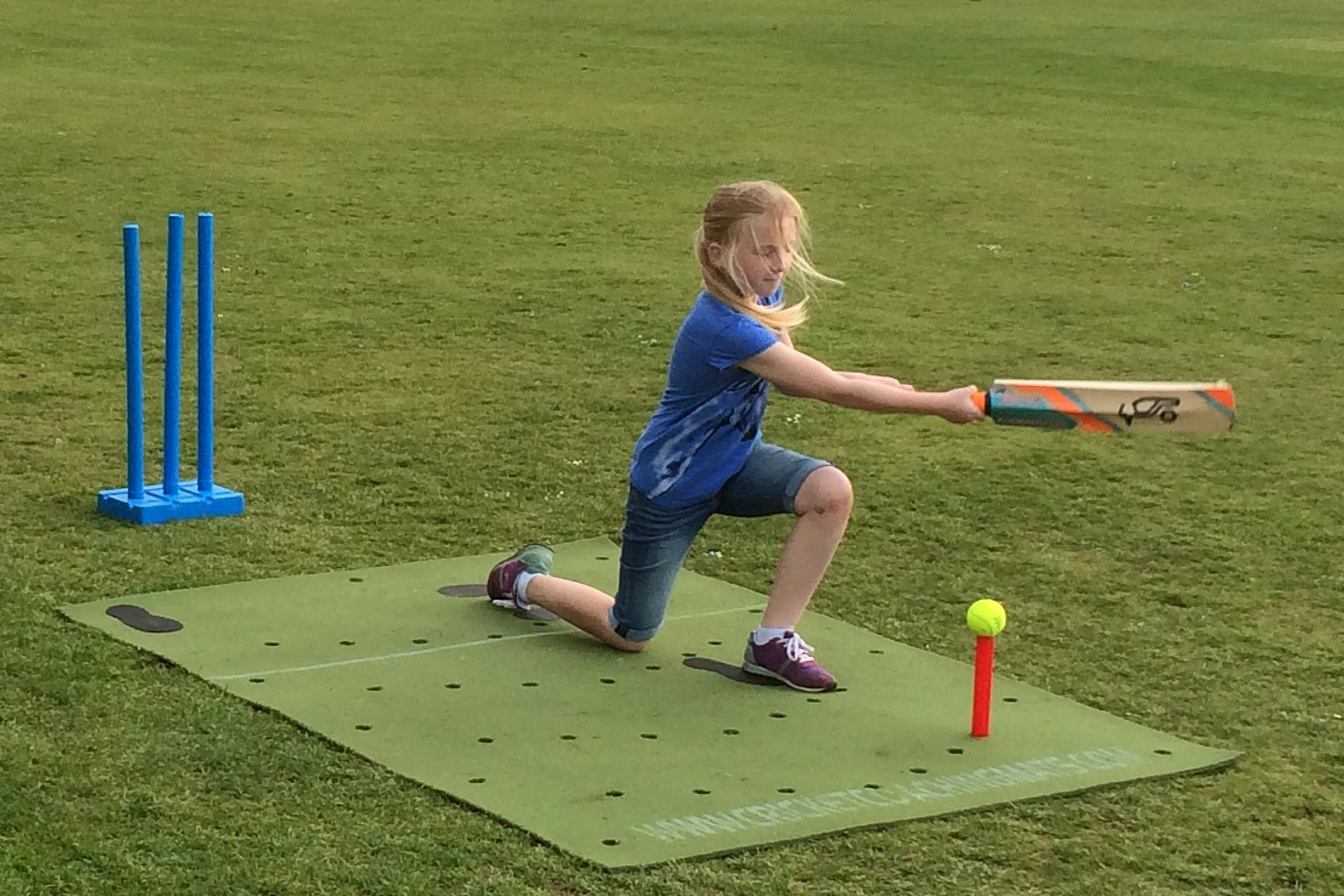 Girls cricket coach. Practice cricket in the garden with the cricket training, practice coaching mat